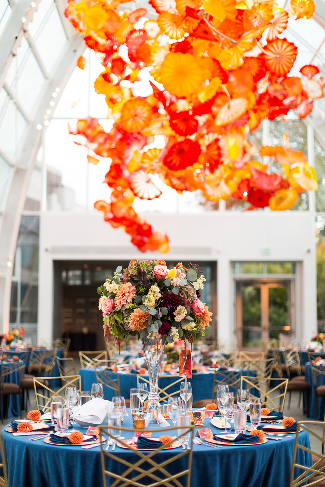 Elevated centerpieces with fall flowers in oranges, Burgundy and yellow colors in the Chihuly glasshouse | Flora Nova Design Seattle