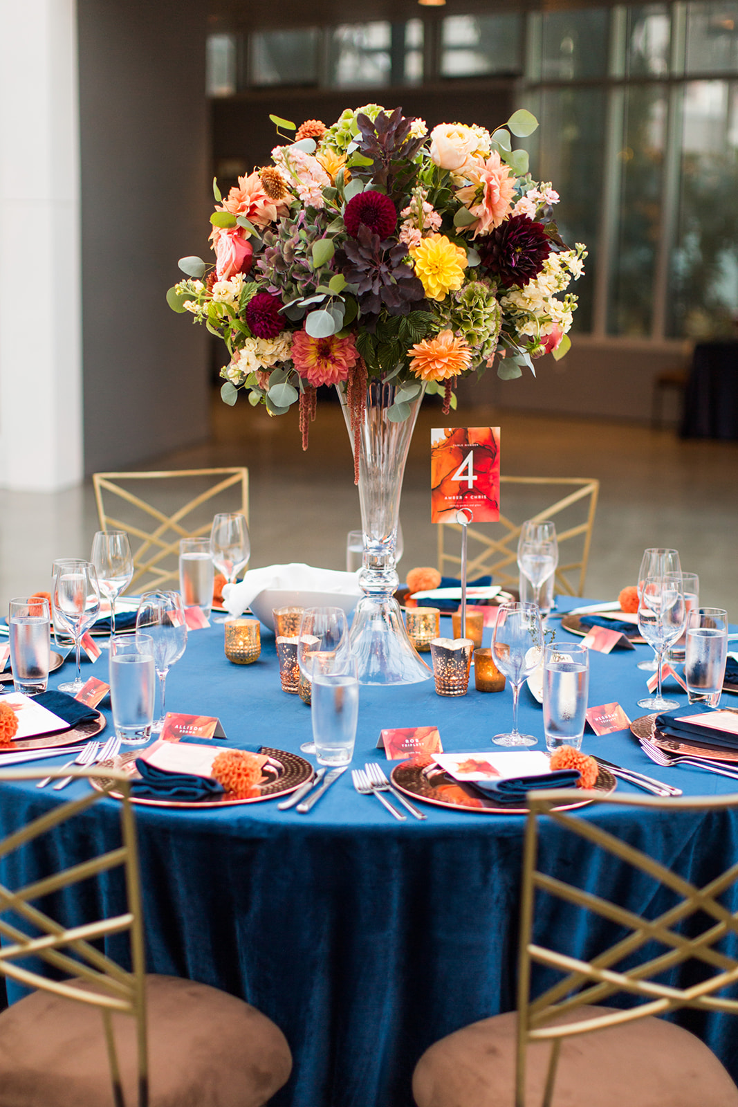 Fall wedding reception in Chihuly glasshouse with navy velvet linens and tall peach and orange centerpieces designed by Flora Nova Design Seattle