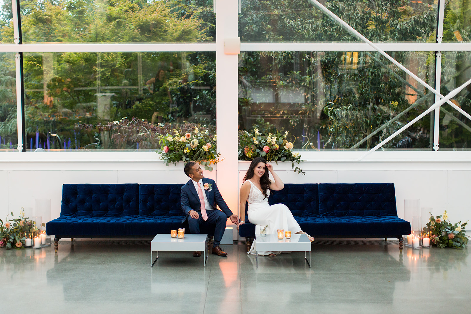Bride and groom sitting on navy blue velvet sofas in a lounge area created for their fall Chihuly wedding