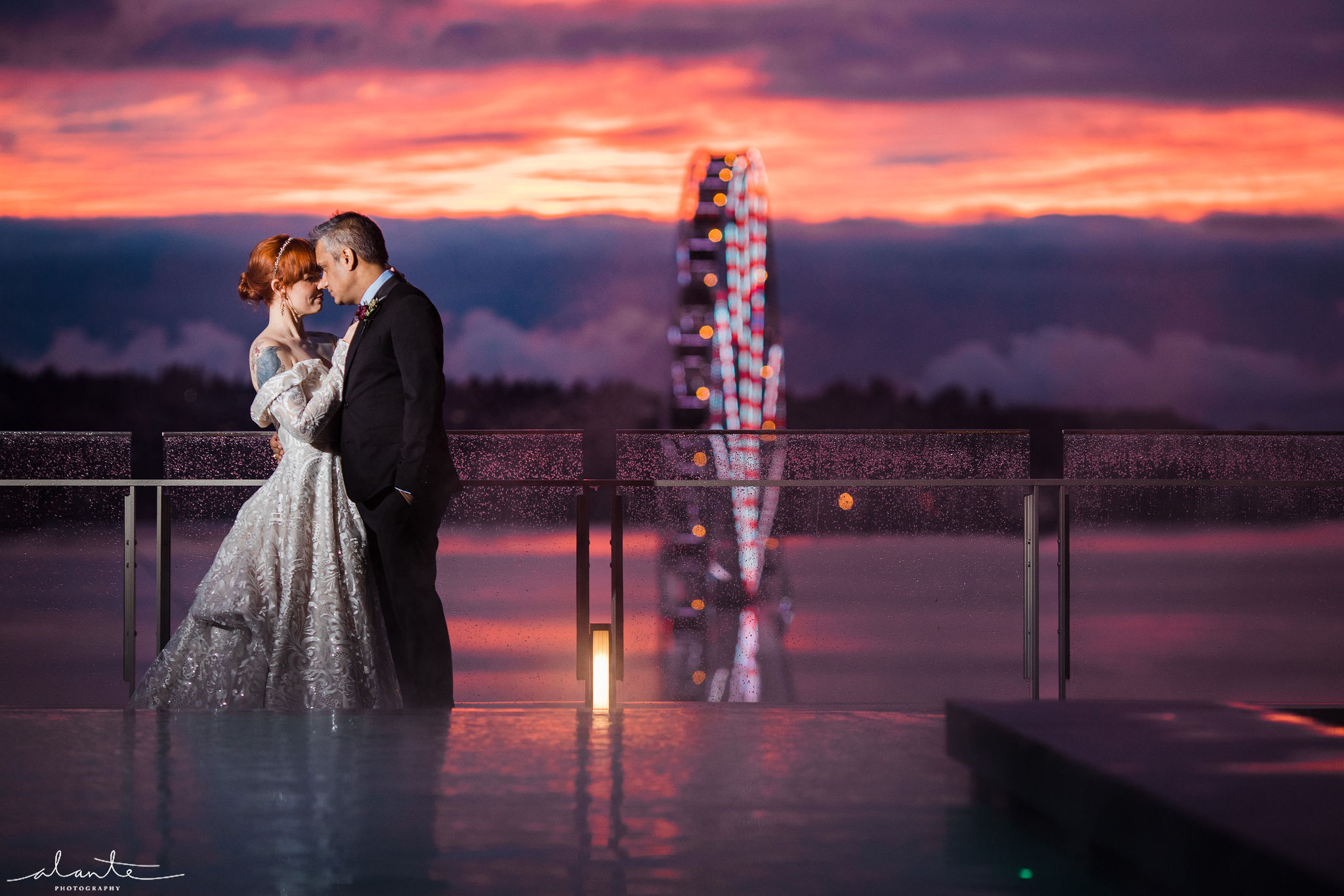Bride and groom in front of the great ferris wheel Seattle at sunset.