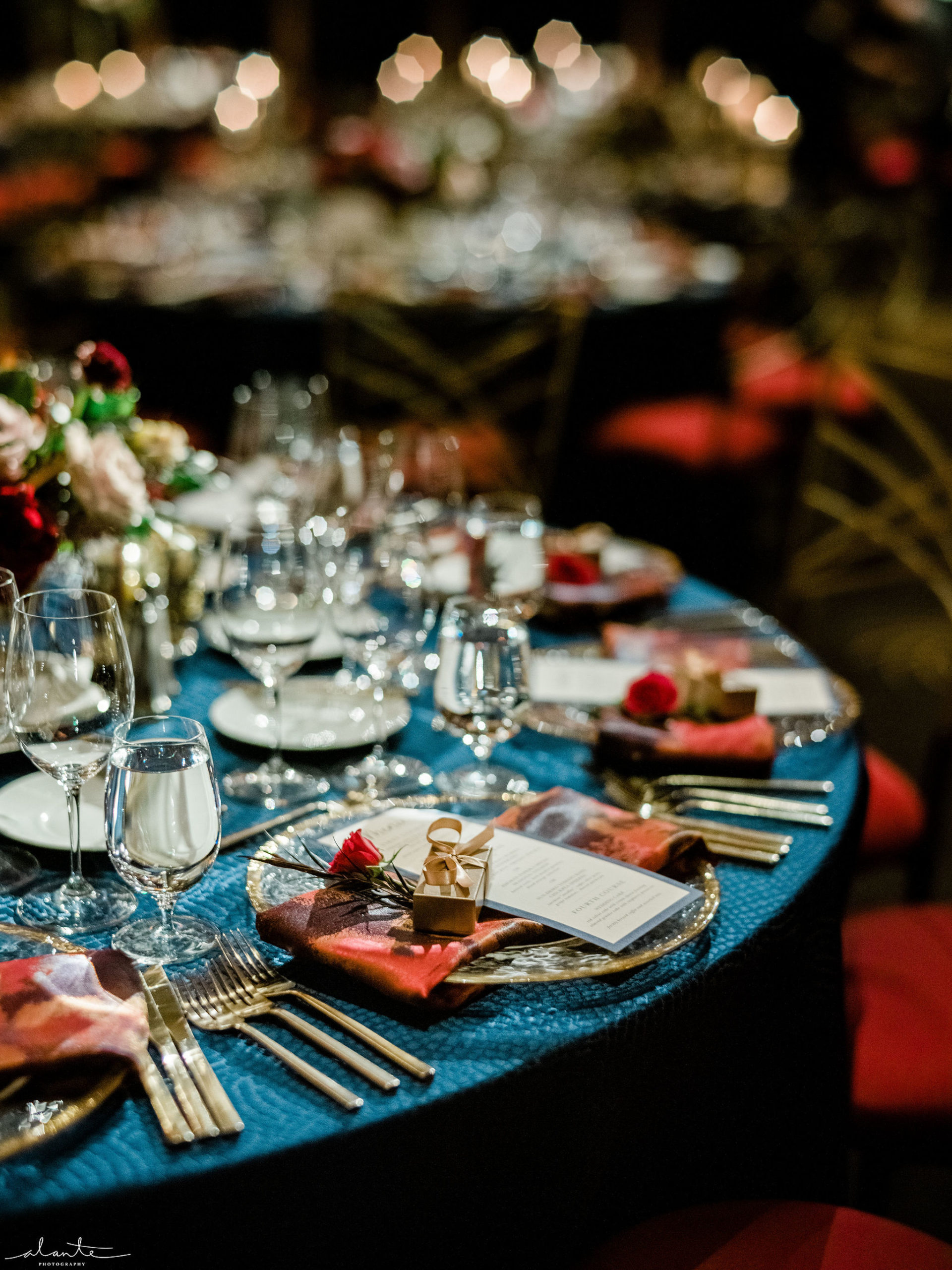 Red winter wedding reception round tables with navy linens and red floral accents.