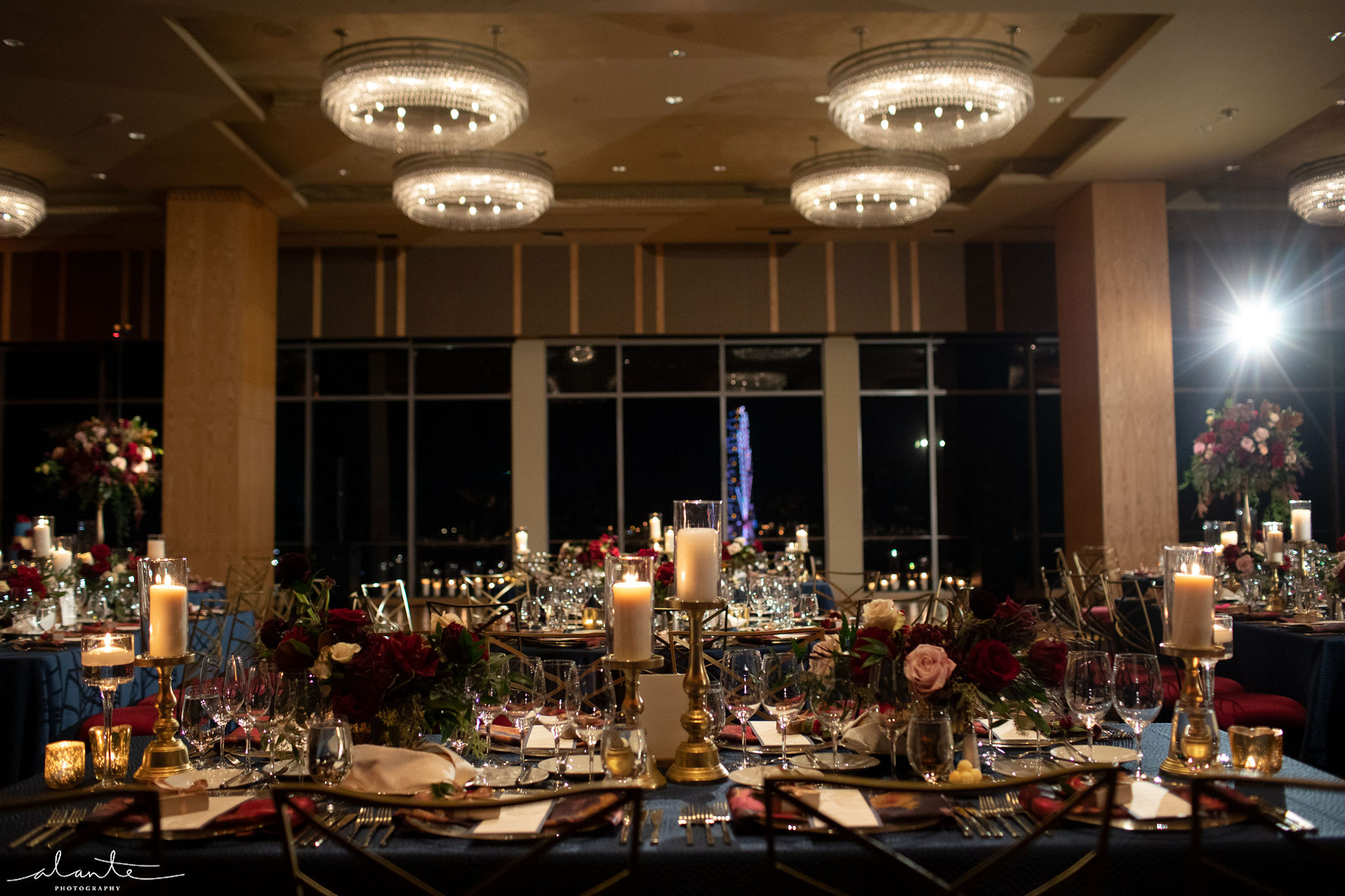 Winter ballroom wedding reception with red and blush floral centerpieces.