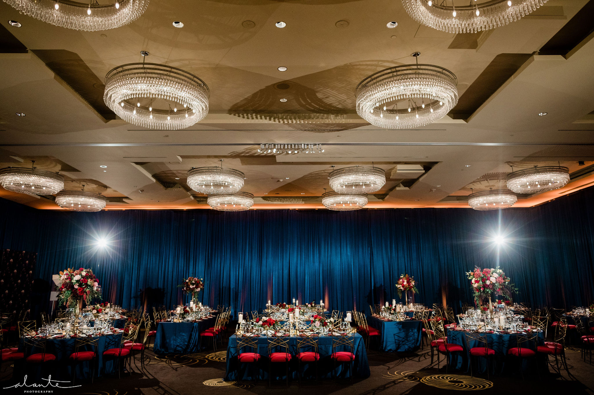 Grand ballroom red winter wedding reception with navy blue draped walls