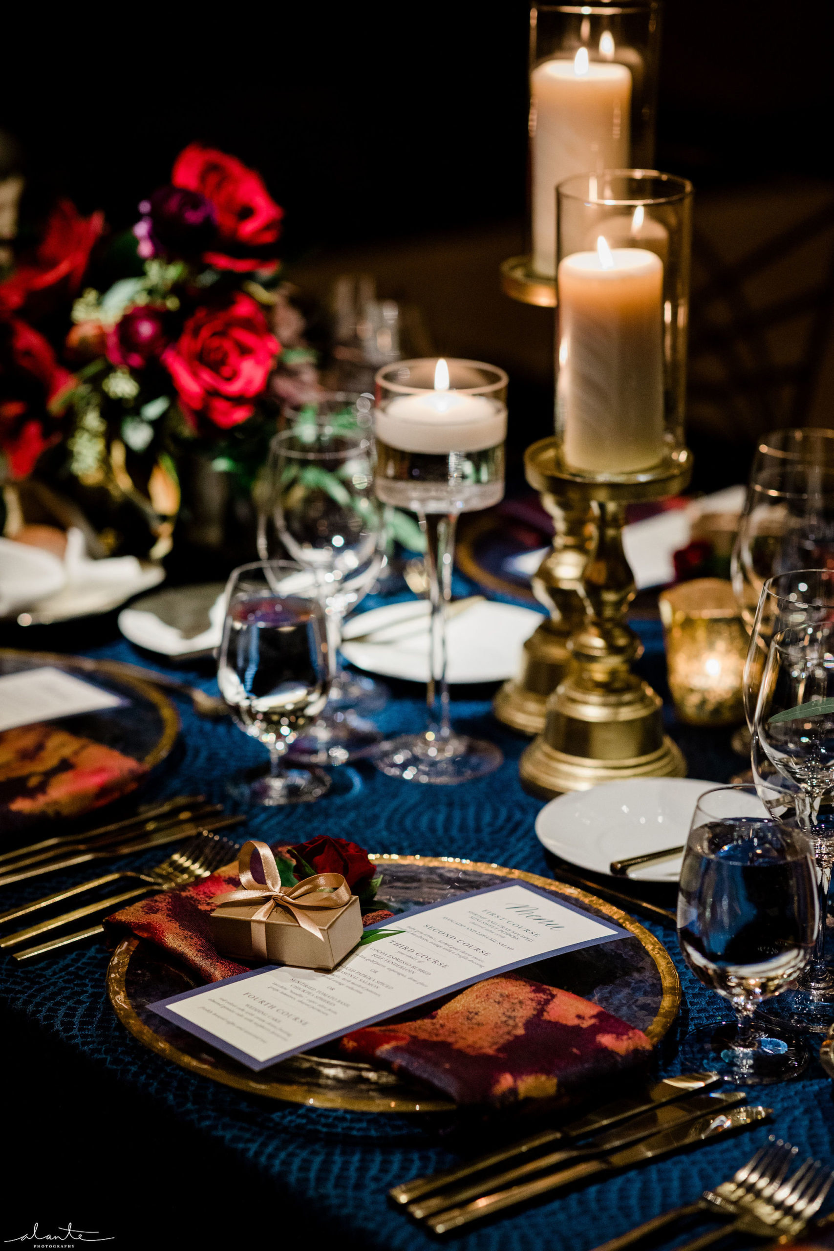 Winter wedding reception table setting of gold flatware and gold rimmed charger plate on navy linen with red rose floral and candles.