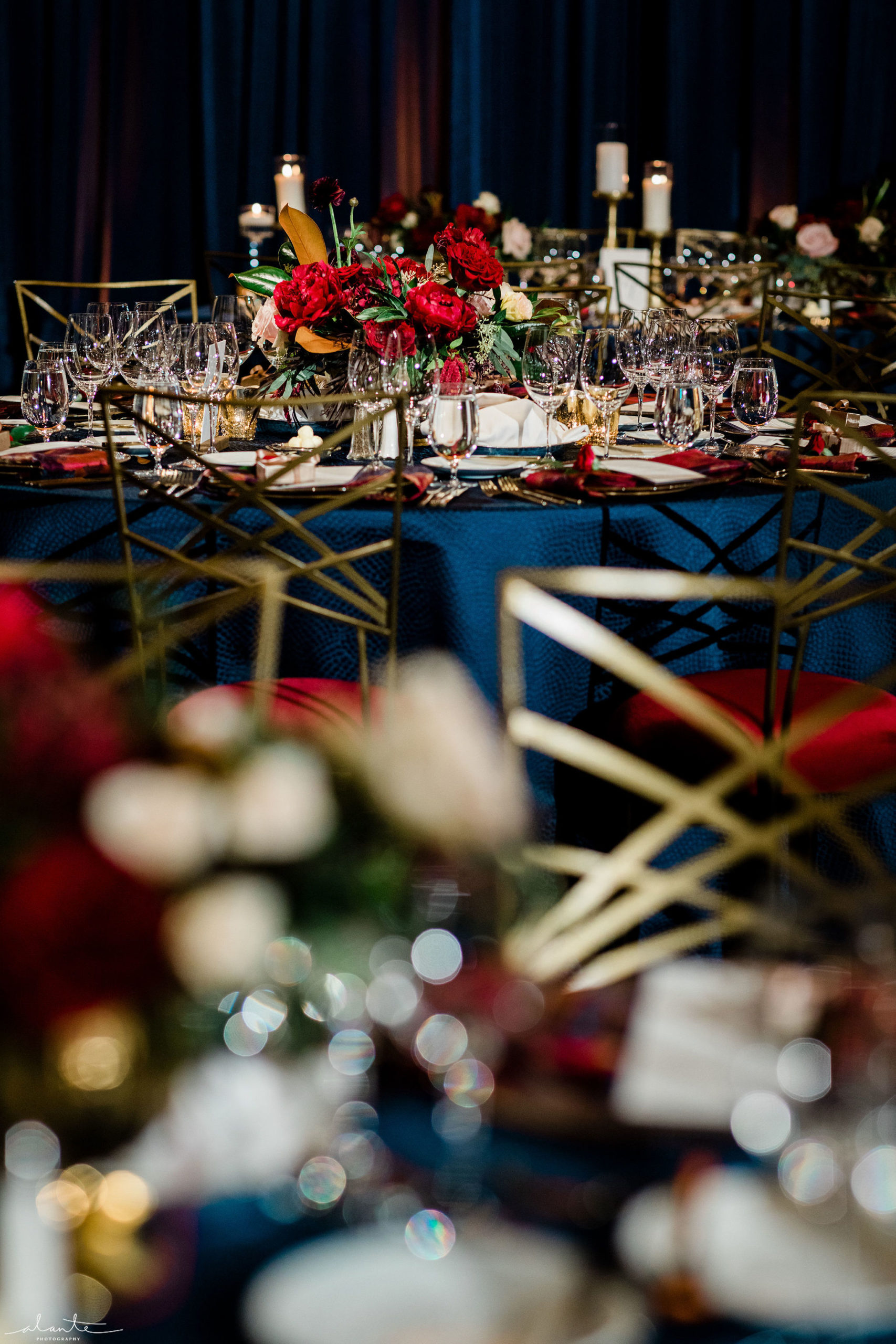 Red winter wedding reception red rose and magnolia centerpieces on navy blue linens.