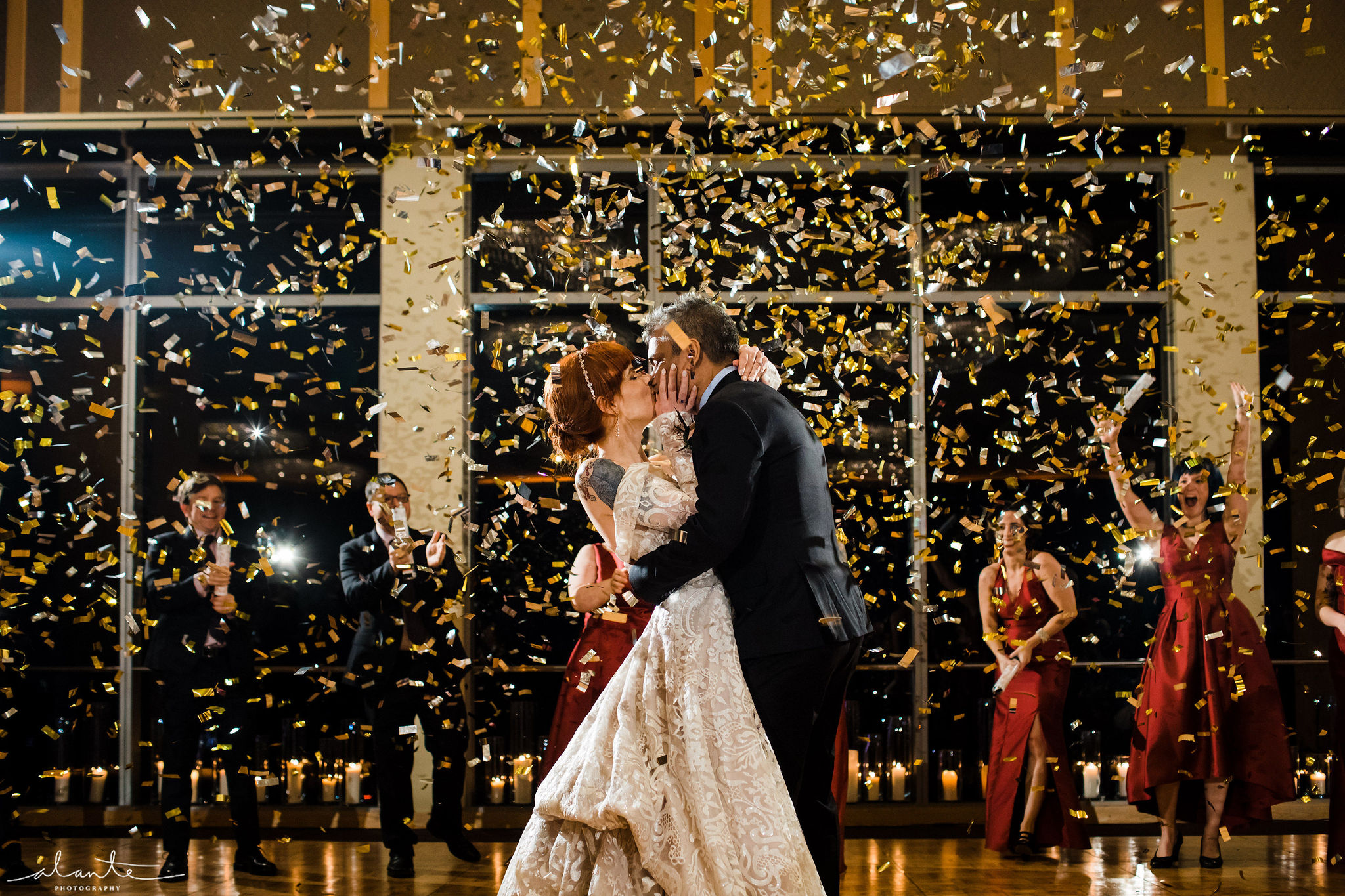 Confetti cannon explodes with gold confetti over bride and groom at their winter reception.