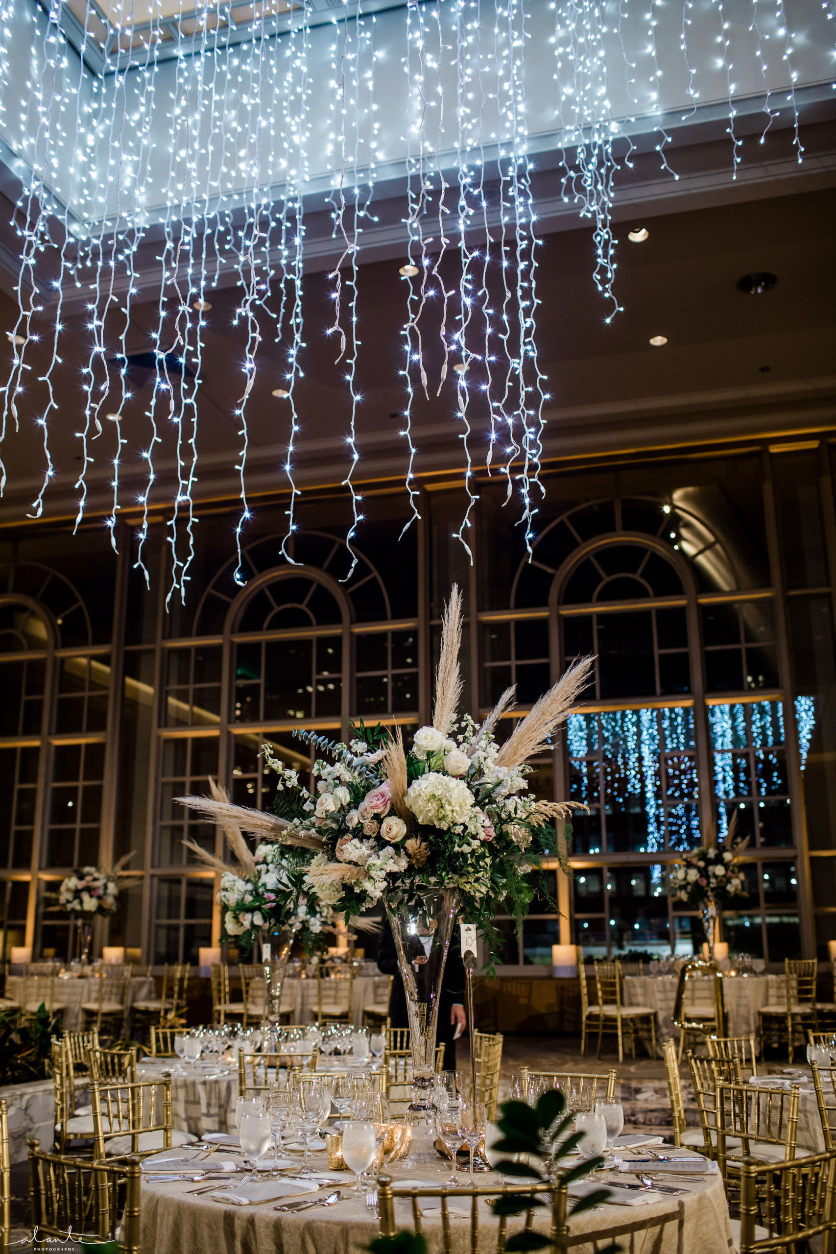 Elevated wedding reception floral with white hydrangea and roses on a tall crystal vase.