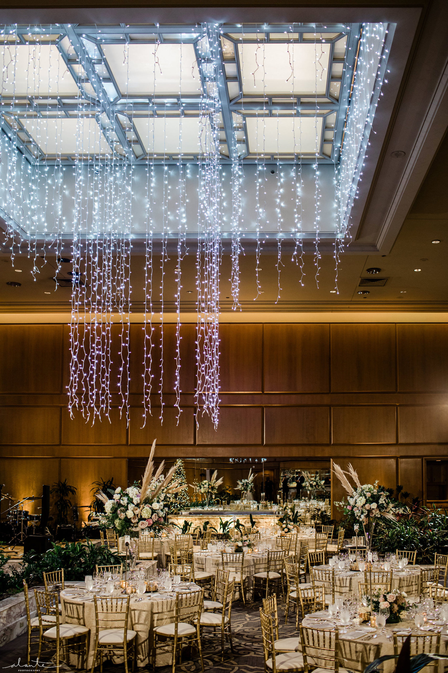 Winter evening ballroom wedding reception with gold chairs and linens under a Christmas light chandelier.
