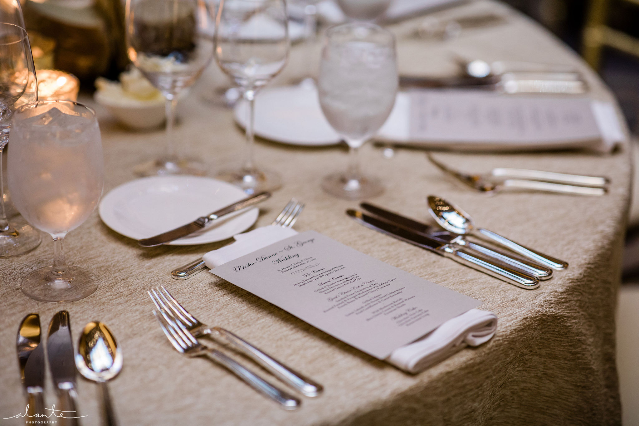Winter wedding place setting on gold textured linens with a menu card on each napkin.