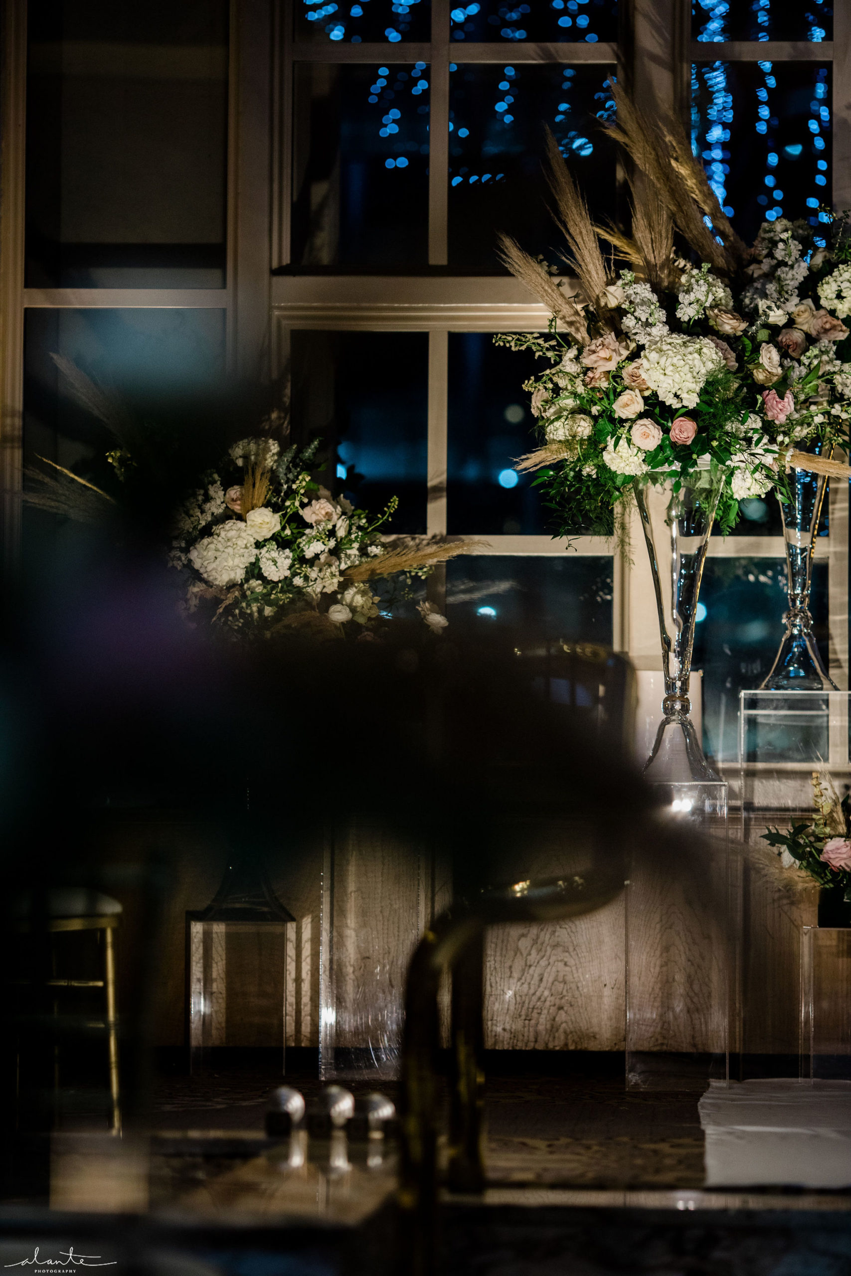 Winter evening wedding ceremony tall alter arrangements on crystal vases.