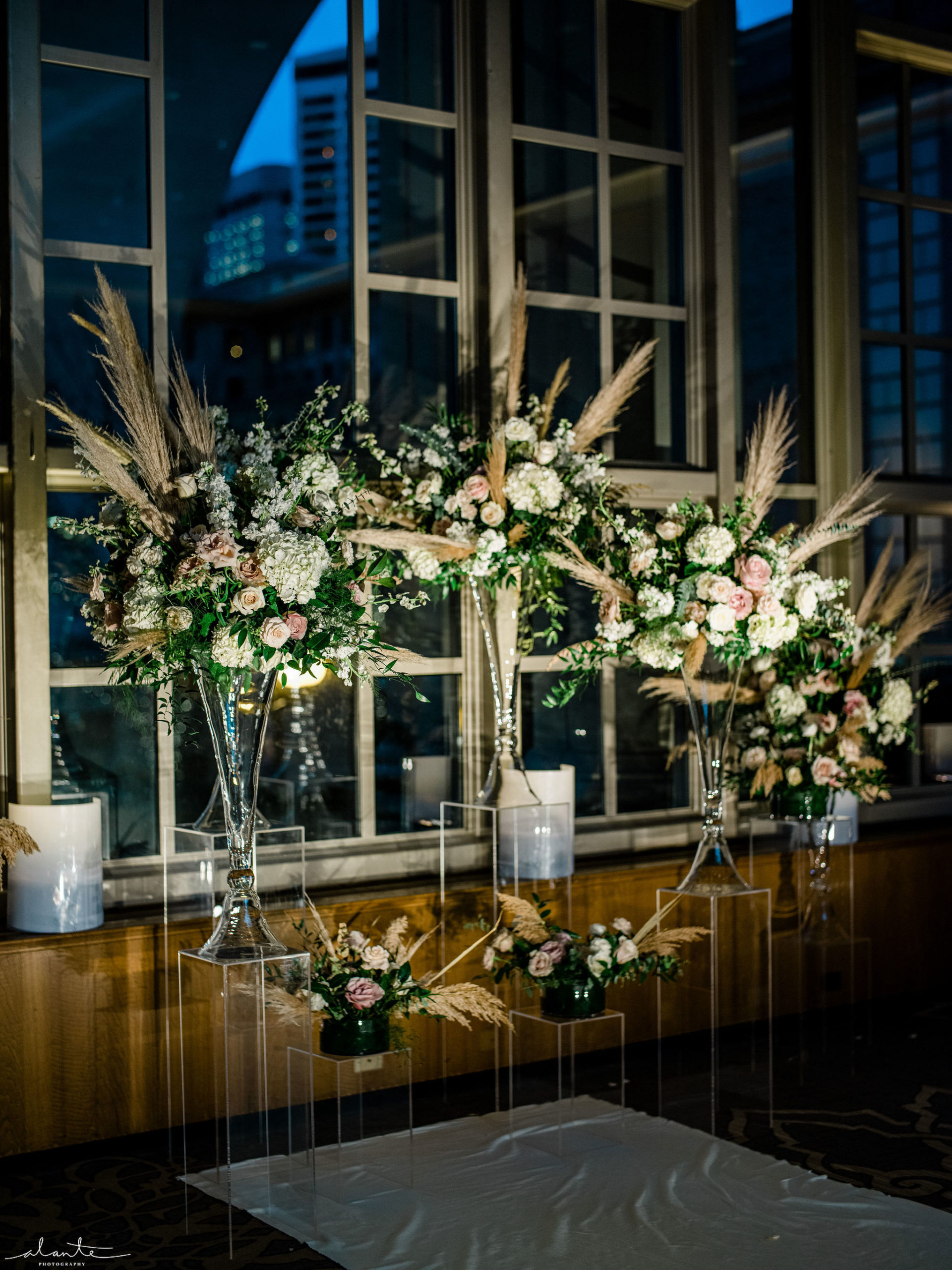 Dramatically lit winter ceremony set up with white and mauve floral grouped up front and placed on Lucite pillars.