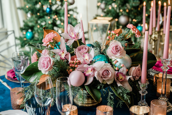 Decorating for the Holidays: Centerpiece for the holidays with pink roses, pink, orchids, pink ornaments, candles, navy linen, in front of Christmas trees