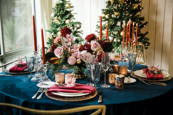 Decorating for the holidays: centerpiece of pink roses, pink orchids, red dahlias, pink ornaments, on table with navy linen, red velvet napkin and red taper candles with Christmas trees