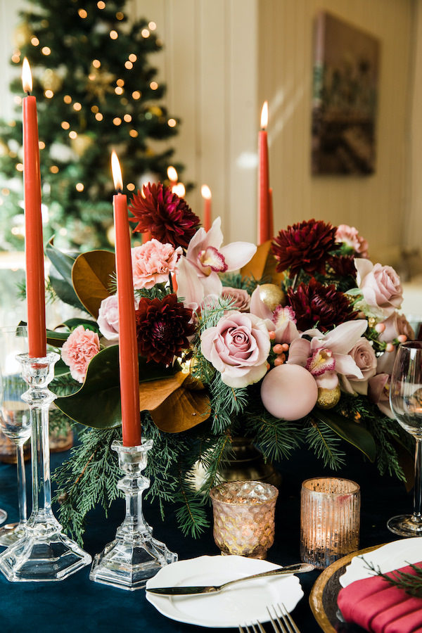 Holiday dinner centerpiece with pink and red flowers, pink ornaments, navy velvet linen, red velvet napkin