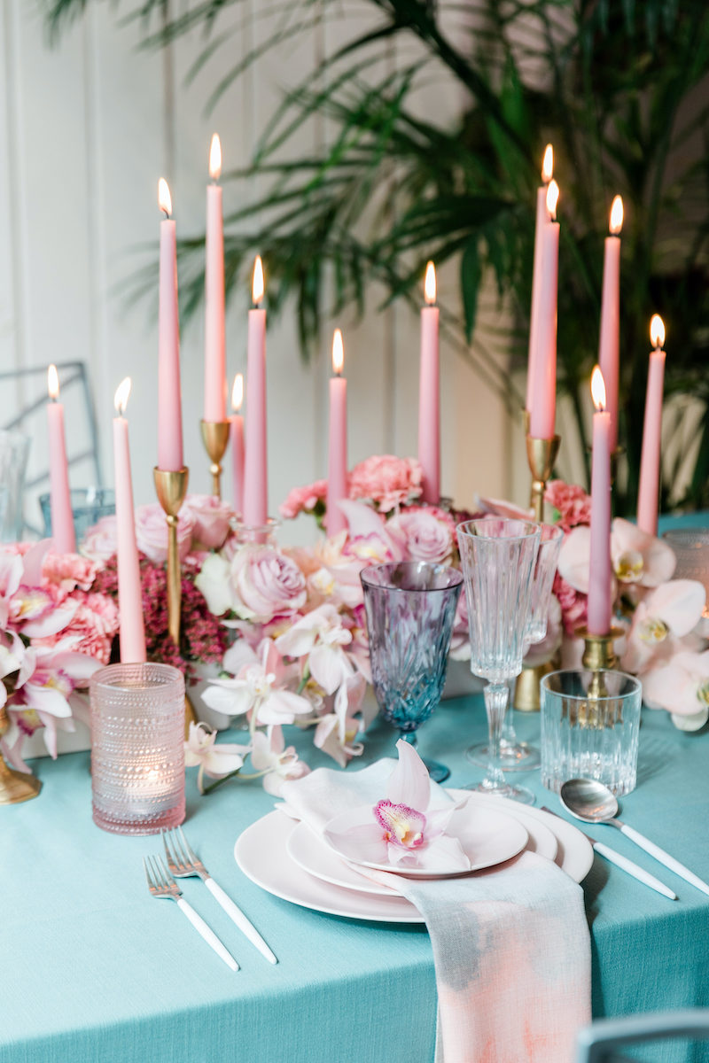 Pink taper candles nestled into a floral centerpiece with every shade of pink flowers placed on a teal linen for a modern dinner party table setting.