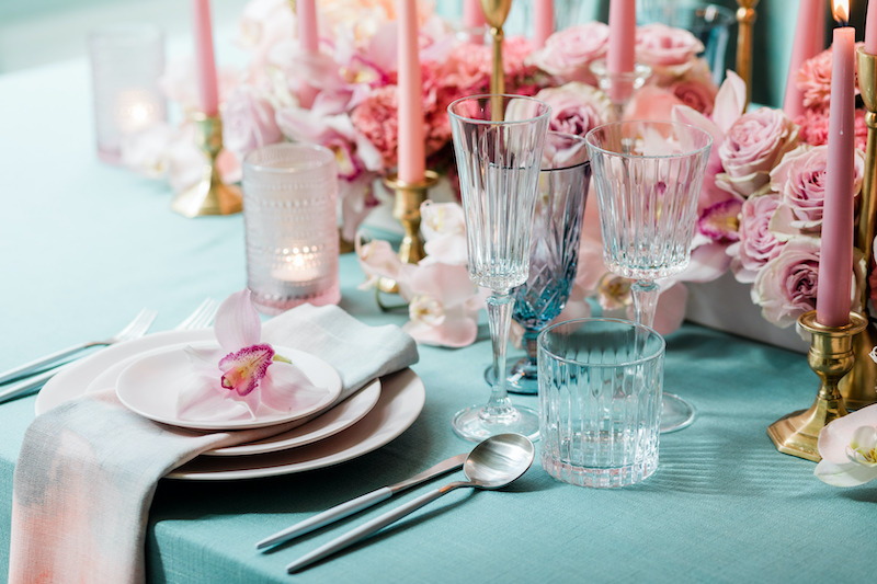 Teal linens, cut glass stemware, and light pink stoneware plates are paired with a low pink floral centerpiece.