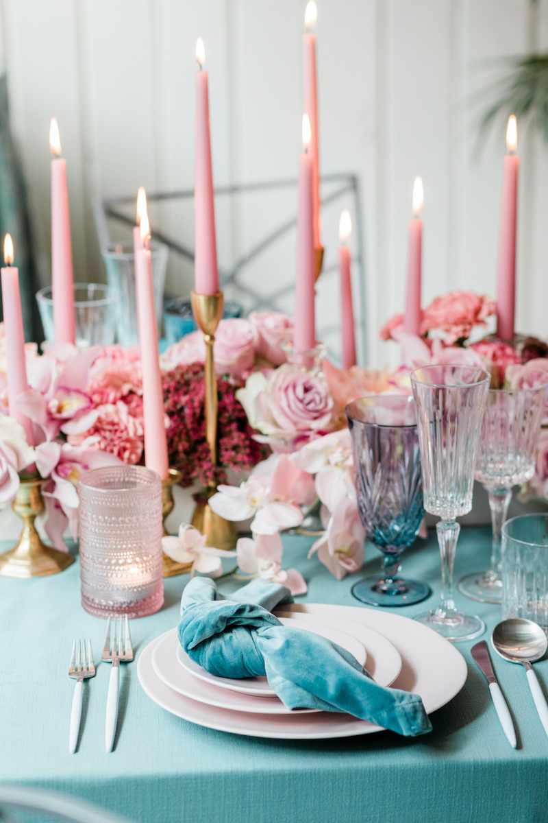 Low pink and mauve floral centerpiece with taper candles tucked in on a teal linen with a teal velvet napkin and pink stoneware plates for a dinner party place setting.