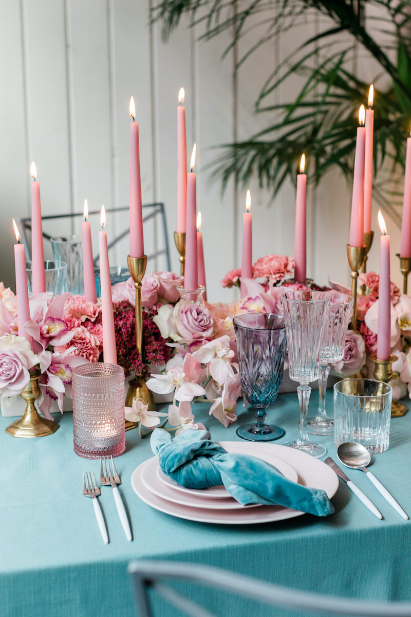 Teal velvet napkin on a stack of pink stoneware plates and lush pink floral for a romantic dinner place setting.
