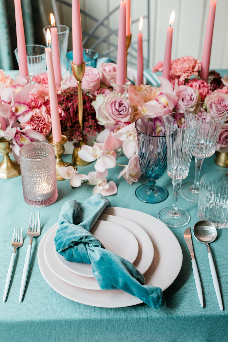 Teal and pink paired for a modern and intimate valentines dinner place setting, with pink floral and teal linens.