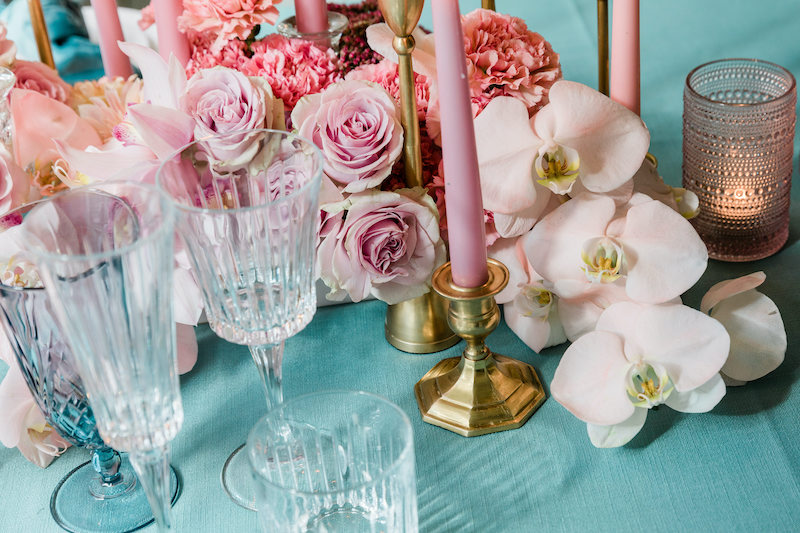 Light pink phalaenopsis orchids spill out of a low floral arrangement of all pink flowers including roses and carnations, placed on a teal linen.