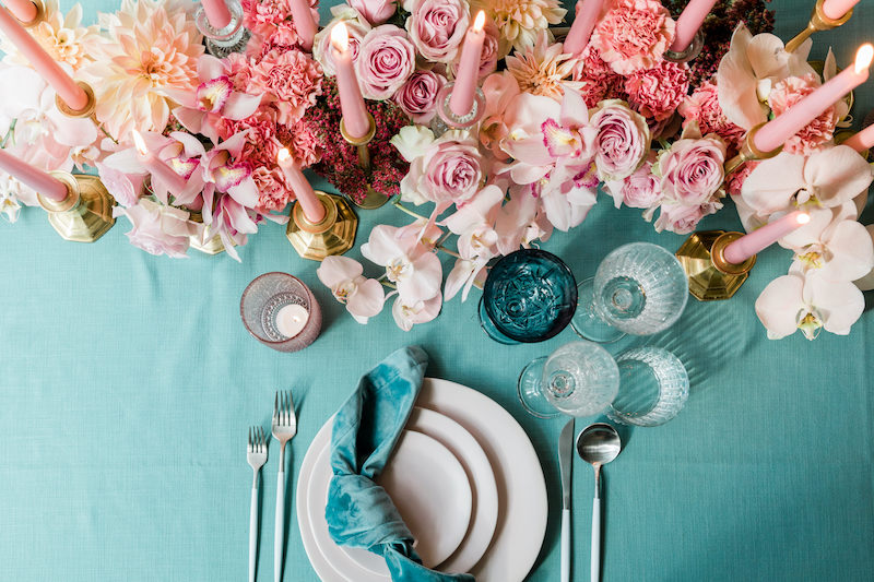 Low runner of pink, blush and peach floral run down the center of a long dining table set with turquoise linens and napkins, along with lots of candles for a romantic party setting.