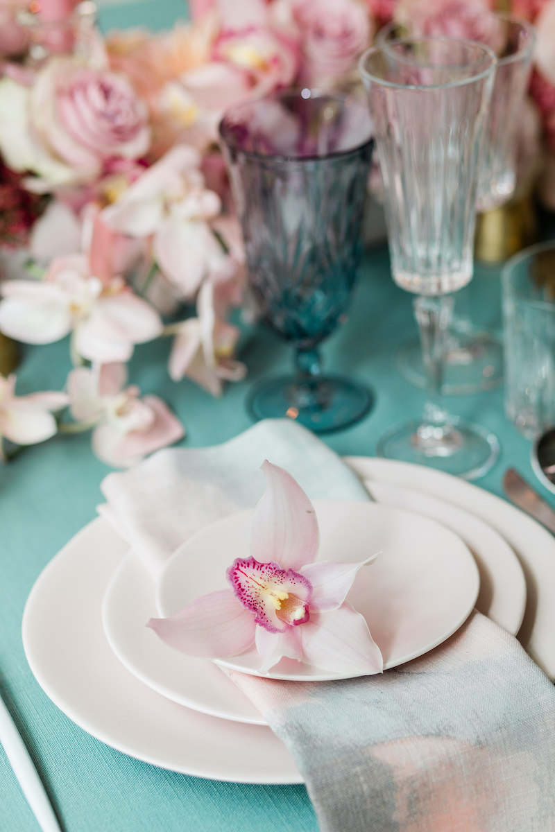 Light pink stoneware plates for a formal dinner party layered with a teal and pink watercolor napkin and a mauve orchid at each place setting.