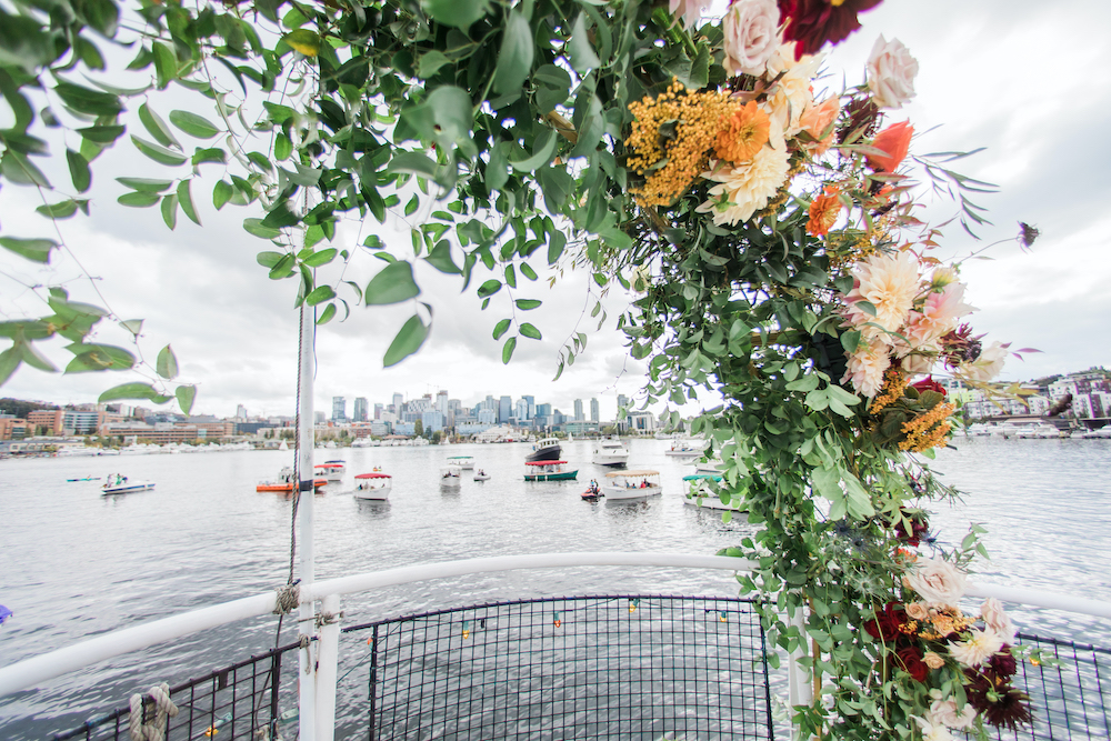 A boat wedding on Seattle's Lake Union with greenery and floral arch and guests on boats