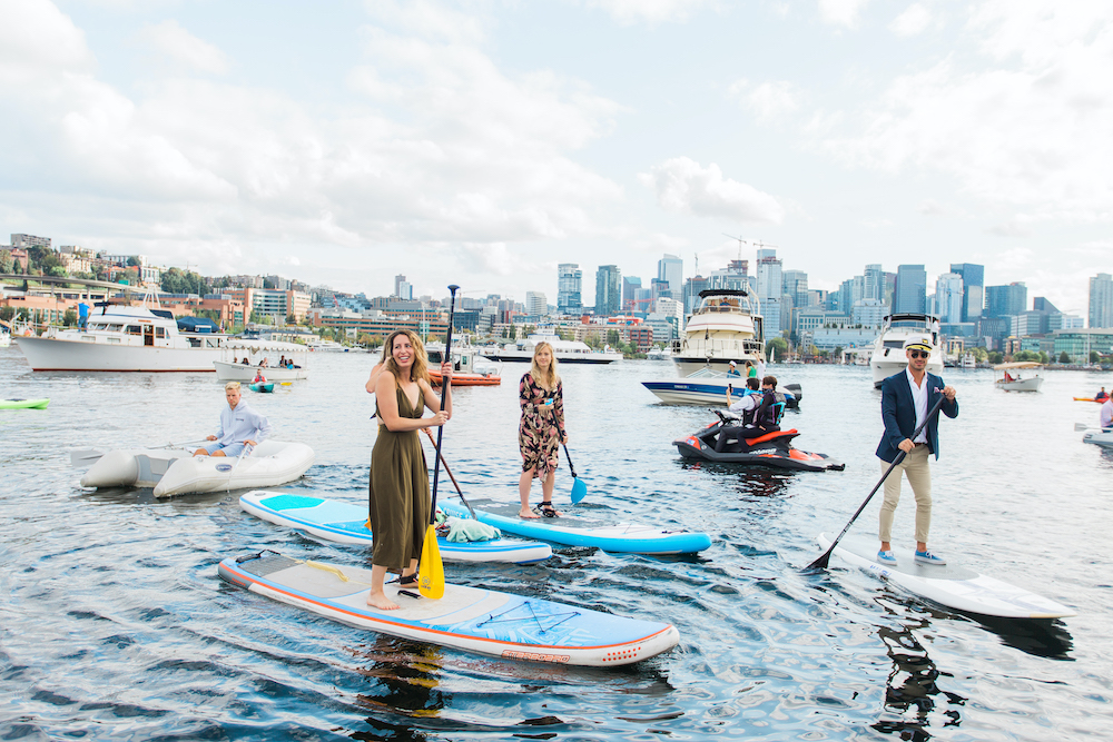 Wedding guests on paddle boards on Seattle's Lake Union during safe pandemic wedding in Seattle