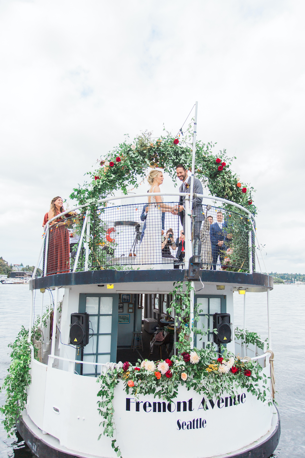 A fall wedding on Seattle's Lake Union with greenery arch and socially distanced guests - a safe pandemic wedding in Seattle