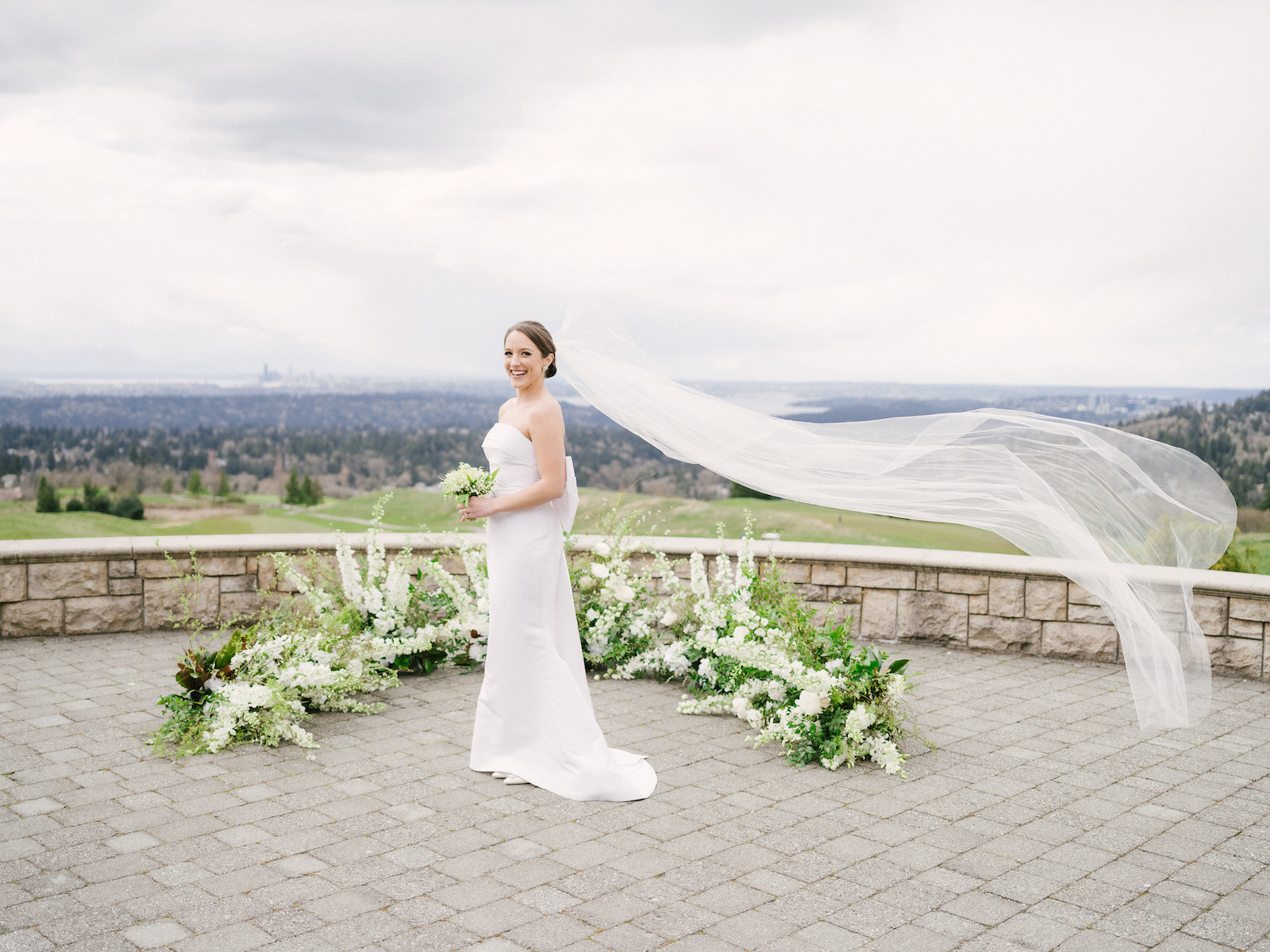 Bride holding a Lily of the Valley bouquet, in front of her grounded wedding floral arch, her veil blowing in the wind