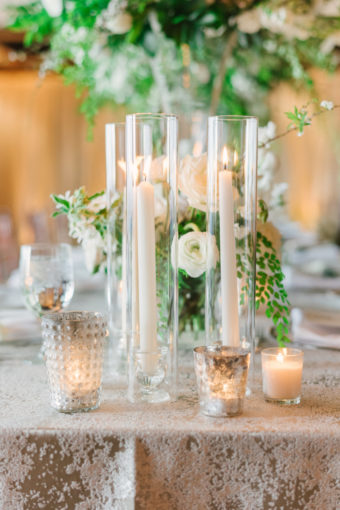 White taper candles in glass chimneys, silver mercury votive candles, and white and green spring flowers for Seattle wedding