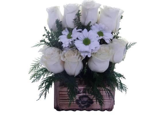 arreglo florar de rosas blancas sobre una florero de madera