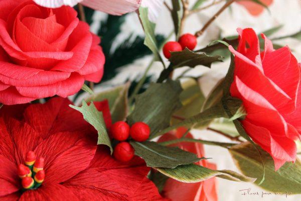 Vista de centro de mesa navideño: acebo, rosas y flores de pascua de papel crepé