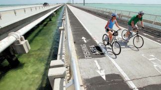 MIKE HENTZ/Contributed Two bicyclists ride across the Lower Sugarloaf Channel Bridge. Many of the Florida Keys bridges need structural work to complete the Florida Keys Overseas Heritage Trail.