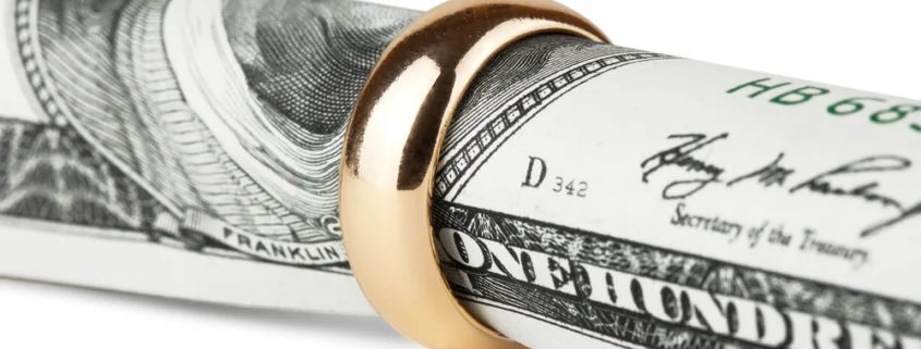 An image of a dollar bill roled up inside a wedding ring to signify alimony in Florida