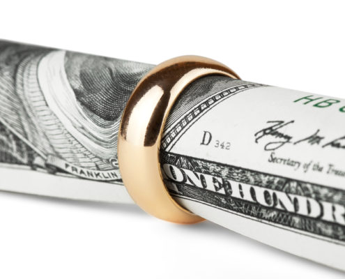 100 dollar bill rolled up with a wedding ring around it to signify prenuptial & postnuptial agreements in Florida