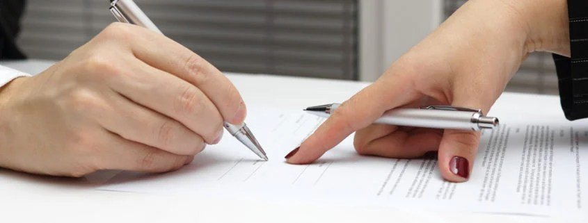 A couple signing an uncontested and collaborative divorce agreement