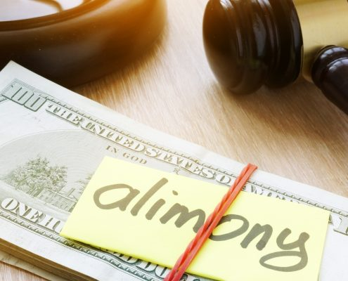 A stack of cash with a sticky note tha says Alimony on it.