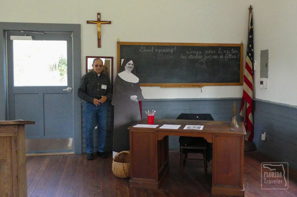 Male docent next to nun cutout in schoolhouse