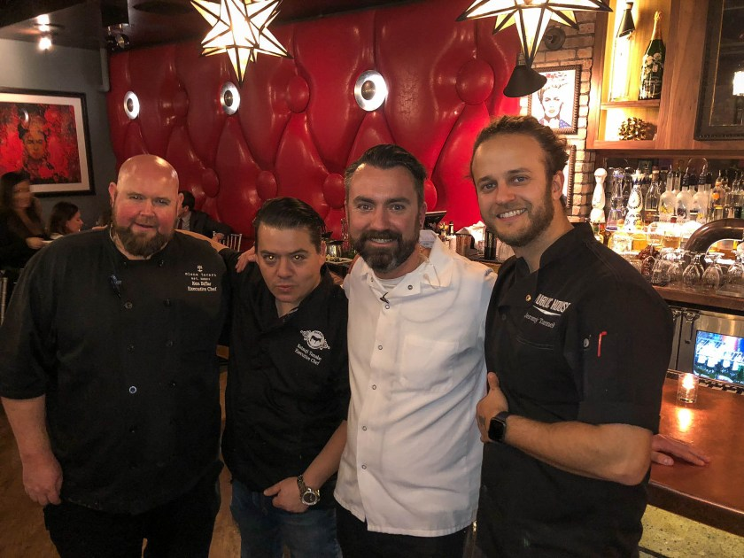 4 Chefs smiling at the camera with their arms around each other