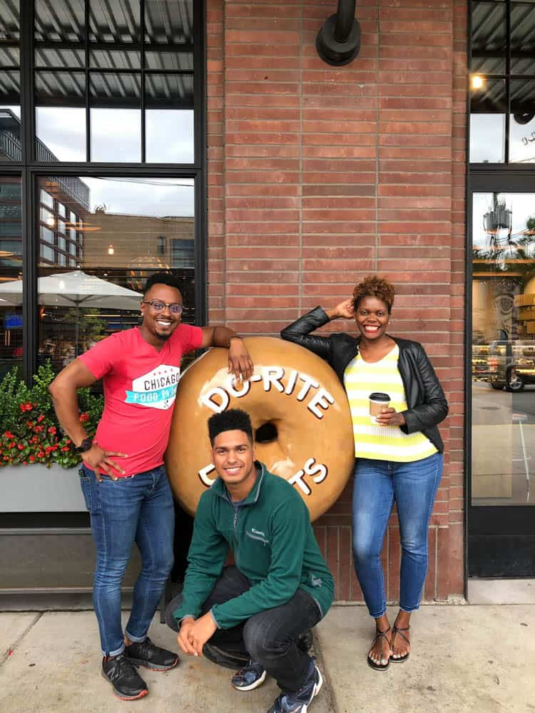 3 people posing next to a giant donut statue