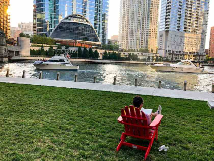 Woman sitting at Chicago Riverwalk reading a book