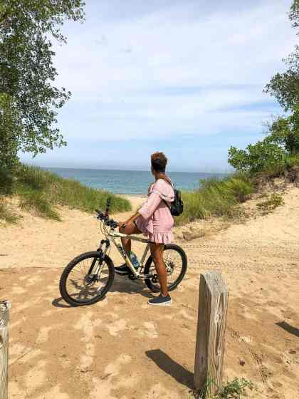 woman on bicycle glancing at the beach