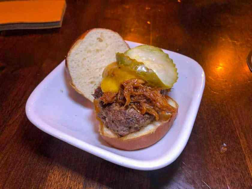 Slider hamburger topped with pulled pork and pickle
