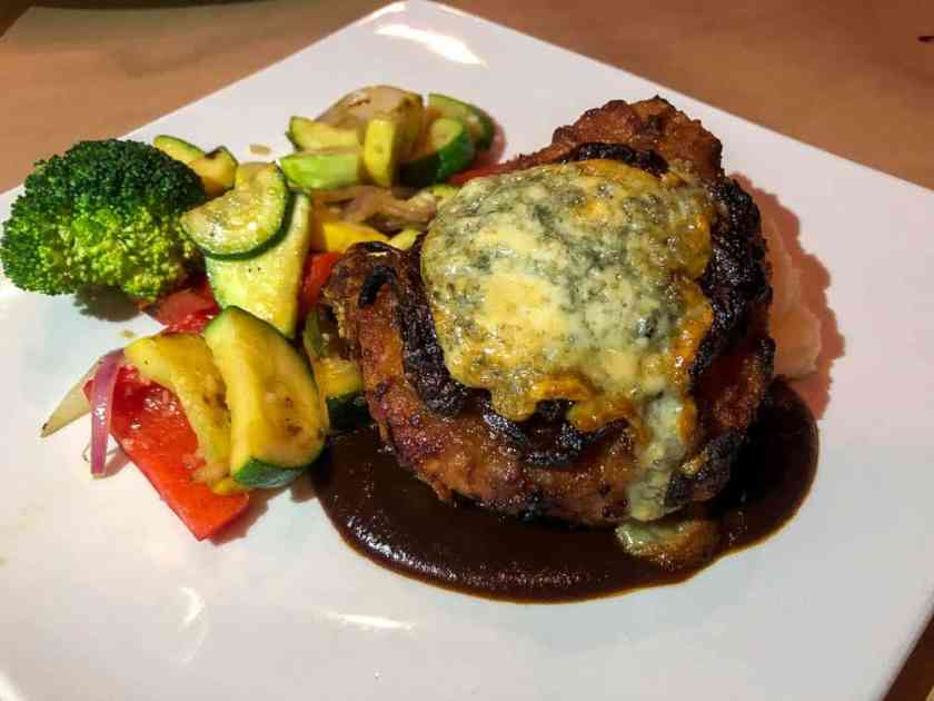 Grilled pork chop topped with blue cheese