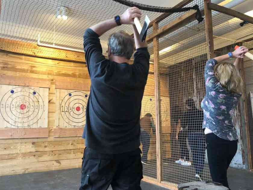 Man and woman throwing axes at targets at Ragnarok Axe Throwing