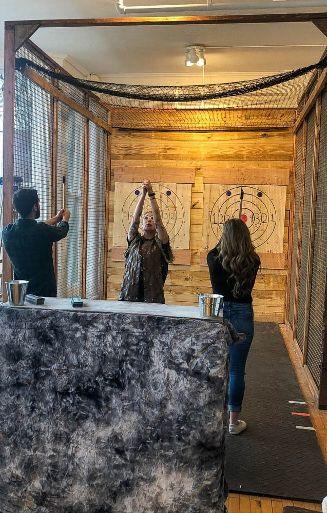 Man and woman throwing axes