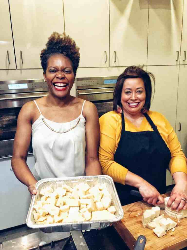 Two women smiling at the camera holding a casserole