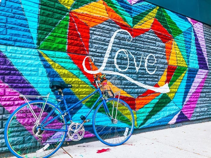Blue Bike resting against a colorful mural