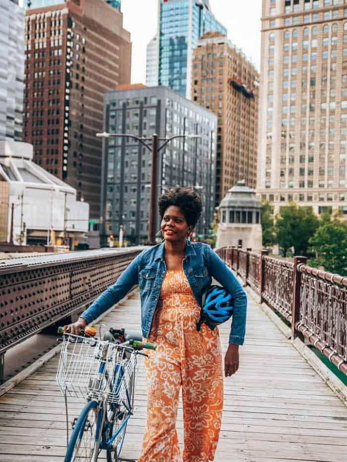 Woman walking blue bike across bridge in Chicago